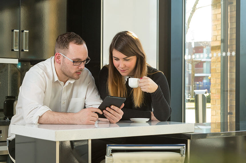 2 pinnacle group employees enjoying a small coffee whilst looking at a tablet