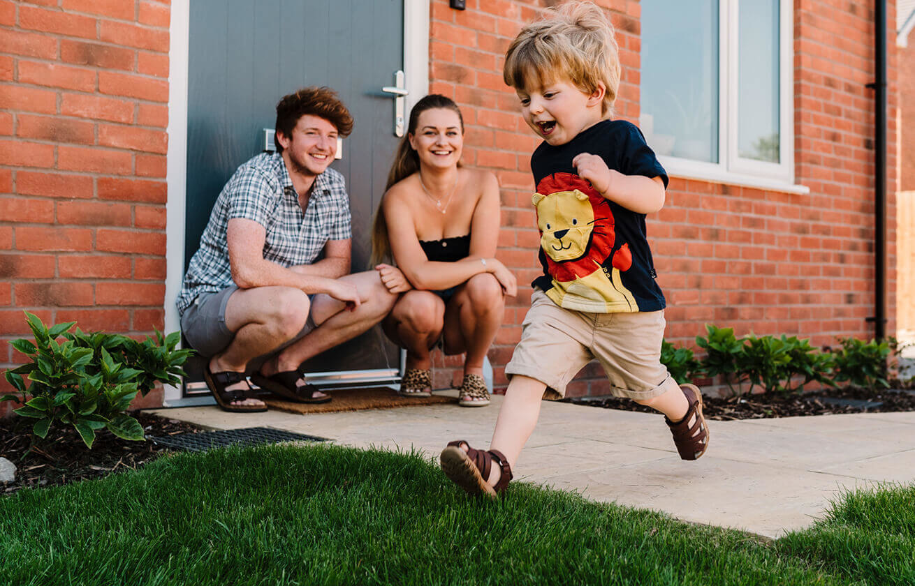 A young family outside a new house, the 2 parents are squatting down whilst a toddler runs