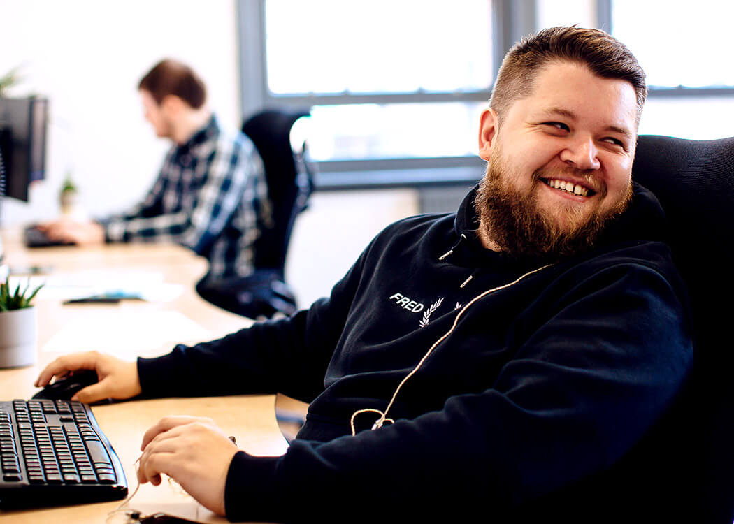 Liam, from Digital Agency Class, looking behind him with a big grin on his face