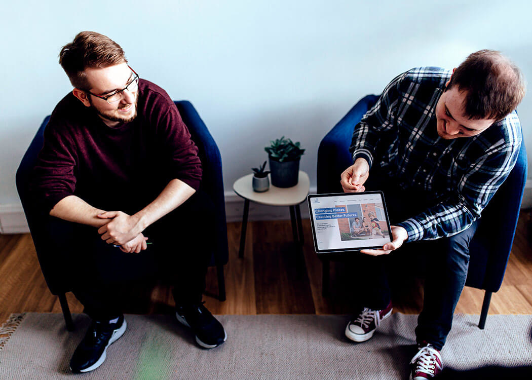 Mirek and Sam, from Digital Agency Class, looking at their web design work on an iPad